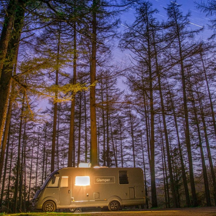 GlamperRV luxury motorhome parked at night in the woods