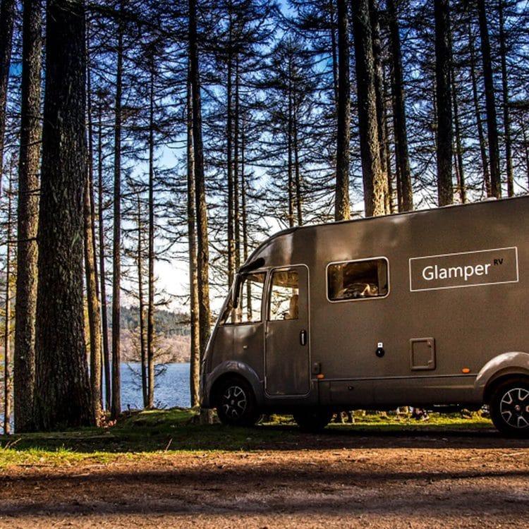 GlamperRV luxury motorhome parked in the woods